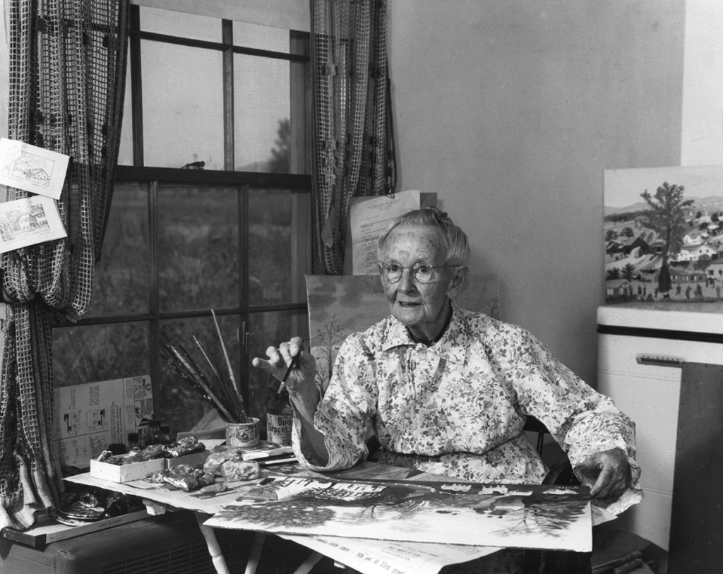Black and white photo of Grandma Moses painting at a table in the room behind her kitchen